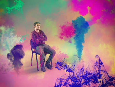 Young man sitting on chair while he visualize colorful ink and steam. The concept of creativity and visualization.
