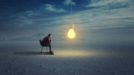 Thoughtful man in wilderness looks to a yellow light bulb coming down from the sky. Stock Photo