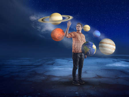 Young man in middle of solar system pointing to a planet into the night.