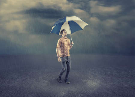 Man hold an umbrella while walk on a rainy day. 写真素材