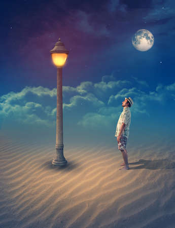 Young man standing on sand looking at an old street lamp under clear moon into the night.