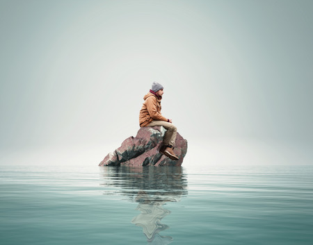 Man stands on a rock in the middle of a sea. Stock fotó