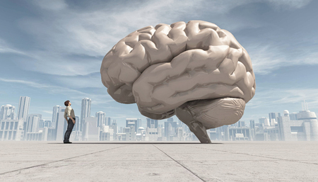 Man looking up to an oversized human brain, with a city far away in the background.