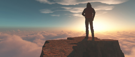 Hiker standing on a mountain cliff above clouds at sunset.