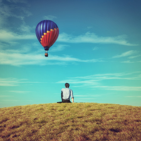 Man sits on grass field admiring a hot air balloon flying to the sky. This is a 3d illustration.