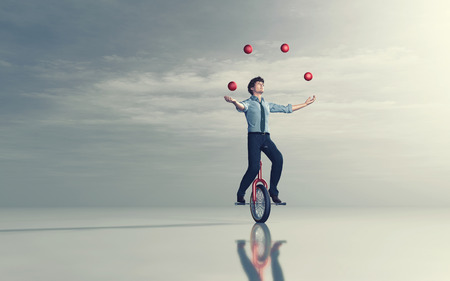 Businessman riding unicycle and juggling with some balls. This is a 3d render illustration Stockfoto