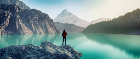 Traveler with a backpack standing on a rock at mountains in front of a lake.