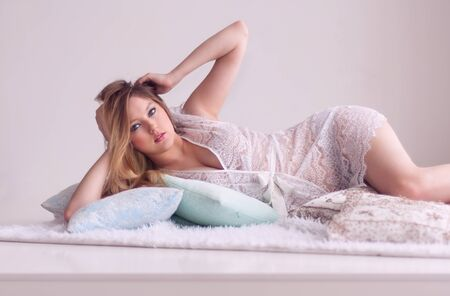 peignoir: blonde in lace peignoir lying on a fur rug