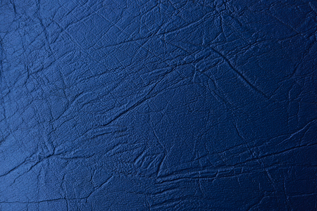A piece of blue artificial leather, with an uneven texture