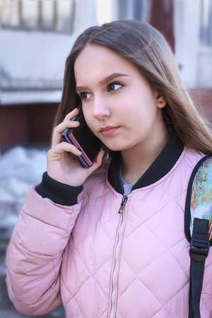A teenage girl in a pink jacket talking on the phone