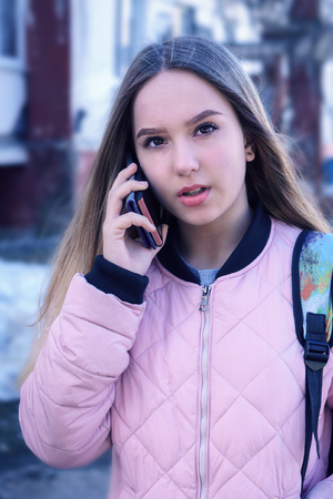 A teenage girl in a pink jacket holds the phone in his hand Reklamní fotografie