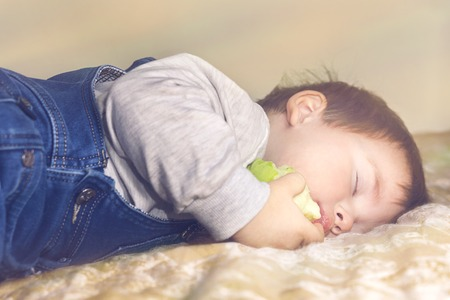 The child fell asleep on the couch with an apple in his hand Banco de Imagens