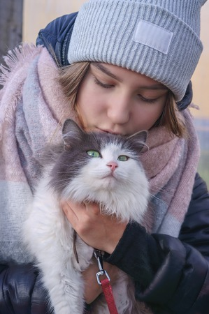 Girl holding a cat in her arms and whispering something to her