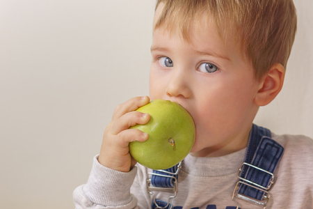 A boy with gray eyes bites a green apple