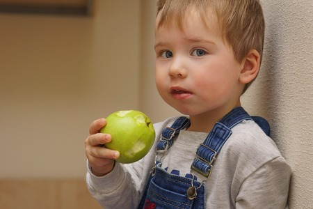 The boy holds an apple in his hand, which he bit off several times
