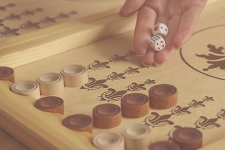 Female hand throwing dice on backgammon board