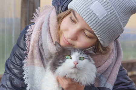 Girl with eyes closed hugs a cat with green eyes and smiles