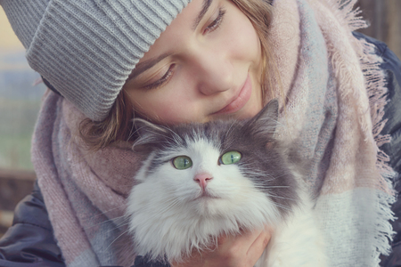 Girl holding a cat with green eyes  in her arms and smiles Banco de Imagens