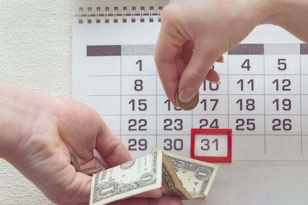People transfer money to each other on the background of a calendar with the highlighted date 31
