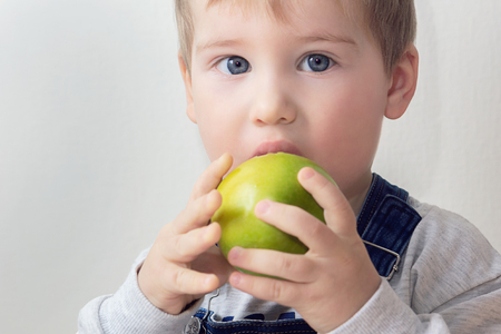 The boy bites a green apple that holds in his hands Banco de Imagens