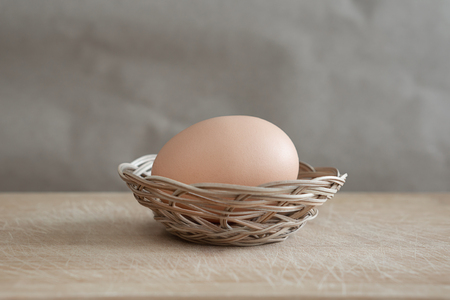 A brown egg lies in a small wicker basket on a wooden table