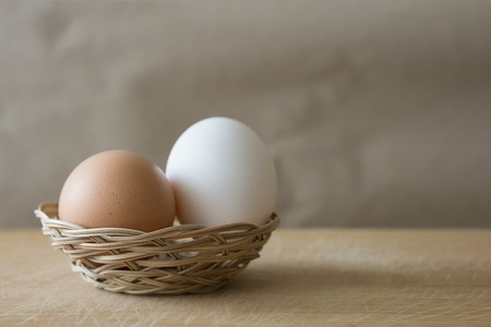 A white and brown eggs lies in a small wicker basket on a wooden table