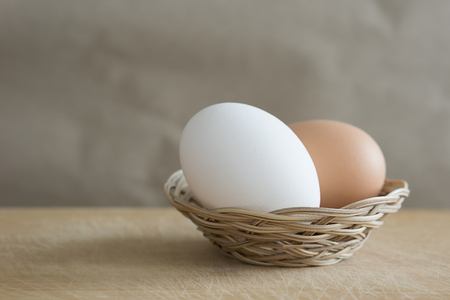 A brown and white eggs lies in a small wicker basket on a wooden table