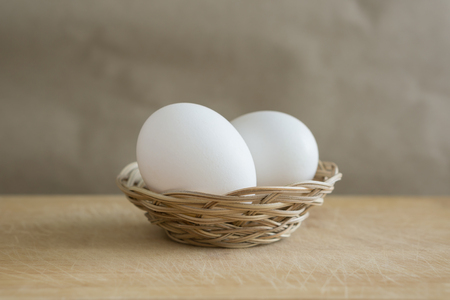 Two white eggs lies in a small wicker basket on a wooden table Standard-Bild - 126960146