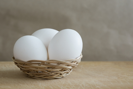 Three white eggs lies in a small wicker basket on a wooden table