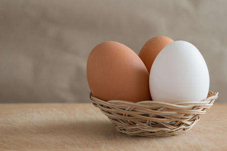 One white and two brown eggs lies in a small wicker basket on a wooden table