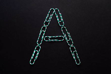 The letter A, folded from paper clips on a black background