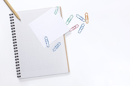 Notepad with a white sheet of paper with a pen and paper clips on white background