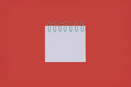 A piece of paper with paper clips attached to it on a red background
