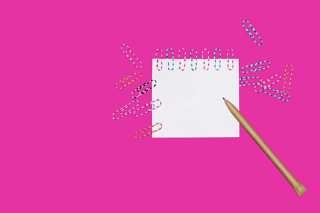 A piece of paper with paper different clips and a pen on a fuchsia color background