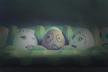 Three eggs with painted faces depict a guy and two girls sitting in the cinema hall