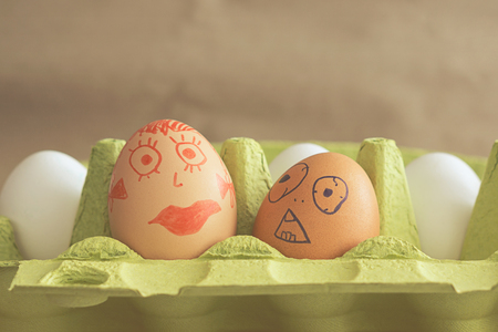 Two eggs, with the painted faces of a guy and a girl, depict a blind date Banco de Imagens