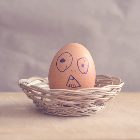 Brown egg with a grimace of surprise or bewilderment painted on it in a basket Banco de Imagens