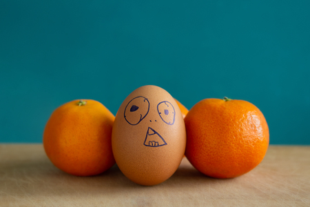 Brown egg stands next to the tangerines. On egg painted surprised face