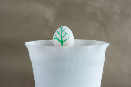 White egg in a flower pot. A green sprout is painted on the egg, symbolizing growth, beginning, new life, spring