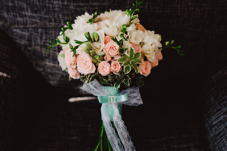 Wedding bouquet stands upright in a chair, black background.