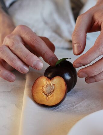 the cook cut the juicy plum and showed