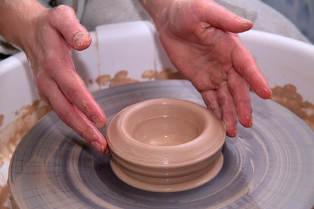 clay modeling: Clay pot on a potter wheel and hands, modeling of pot hands, the sculpting of the hands
