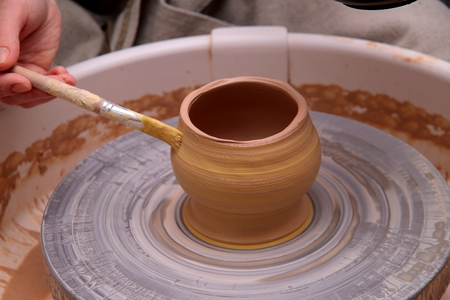 clay pot: Clay pot on a potter wheel, modeling of pot hands, the sculpting of the hands Stock Photo