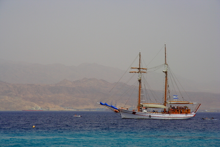 Walking on a wooden boat in the Red sea, Israel, with their sails, and mountains in the background Stock Photo