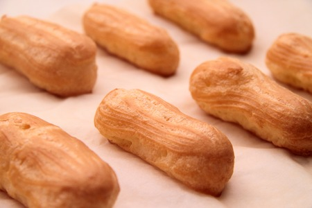 Long rows Eclair shells. Eclairs candy paper. The process of making cakes.