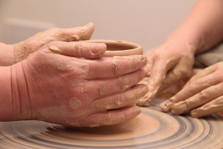 Hands of a potter, creating an earthen jar on pottery wheel.