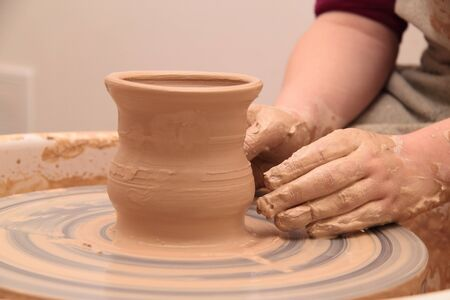 moulding: Hands of a potter, creating an earthen jar on pottery wheel.
