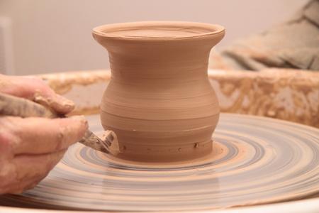 Hände eines Töpfers, eines irdenen Krug auf einer Töpferscheibe zu schaffen. Standard-Bild - 77385150