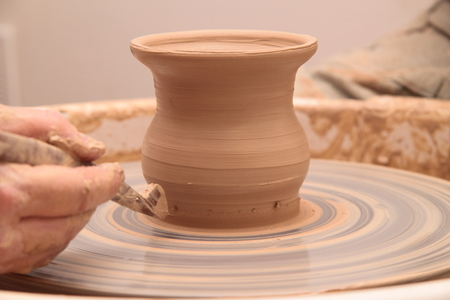 Handen van een pottenbakker, het creëren van een aardenpot op aardewerkwiel.