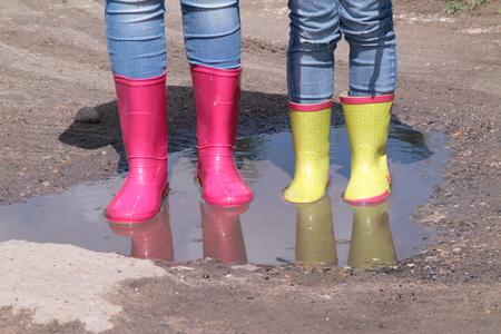 太陽の下で水たまりのゴムは雨でジーンズで子供の足ブーツは立っています。